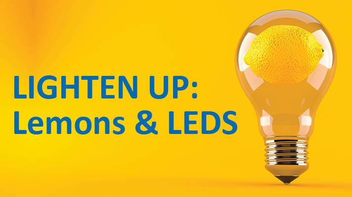 A lightbulb with a lemon inside it on a bright yellow background. Green text reads LIGHTEN UP:Lemons & LEDS