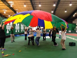 Volunteers and athletes dance underneath a parachute. Photo by Pam Segura
