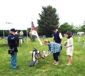 Beth Ballard placing single red rose on grave of Private Cupp