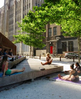 A group of people does yoga in front of the Story Wall at the Rail Park