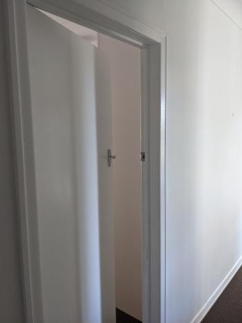 An open door in a white hallway