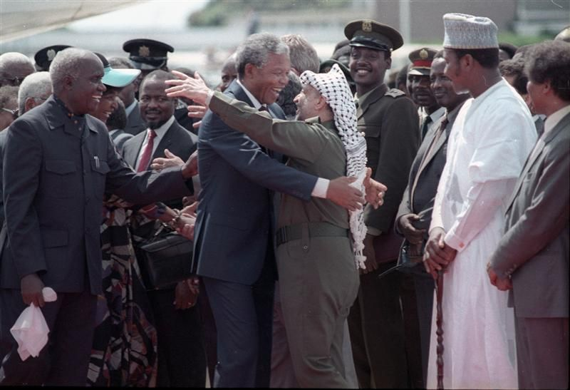 Nelson Mandela (L) is embraced by PLO leader Yasser Arafat as he arrives at Lusaka airport February 27, 1990.  REUTERS/Howard Burditt