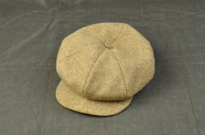 016/028 - Men's cap. Fawn. worsted., twwedwelted. Covered button on peak of crown. The crown is stitched down at the middle of the peak to give a slouched look.Crested label inside crown 'Superior to Any/Equal To Any'. The name of owner is handwritten inside - Danny Masters