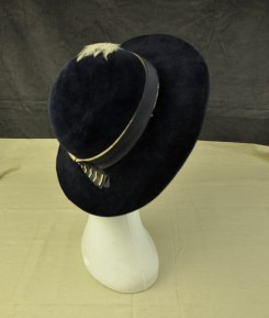 016/007 Women's hat. Navy blue velour with wide brim. Only trim is navy and beige grosgrain ribbon band with pleated tab on back and beige coloured display of feathers on front left.No label or lining trim of any kind.