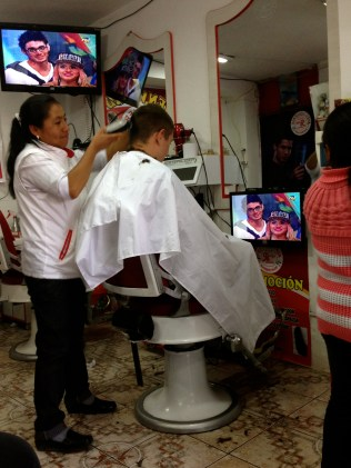 The woman cutting his hair.