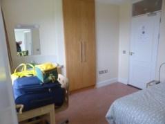 Typical dorm room, desk, bed, vanity, wardrobe. Oh, and peekaboo window over door!