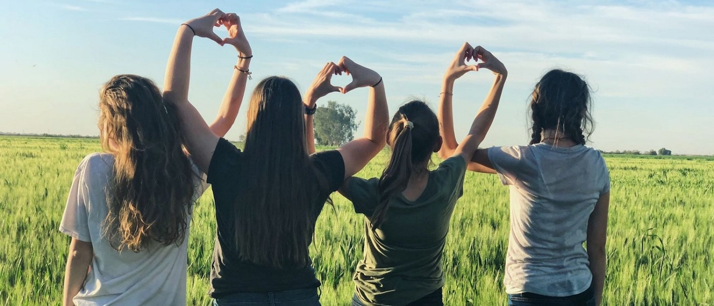 group of young girls with interlocking arms making heart shapes