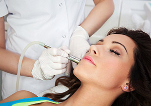 Woman getting laser face treatment in medical spa center, skin r