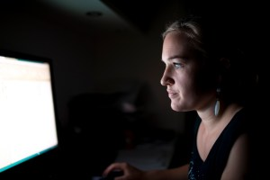 A woman looking at a computer screen in the dark