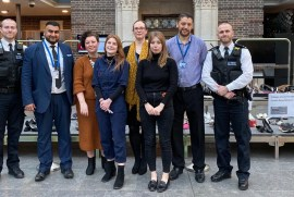A group of Middlesex staff and two members of the Police stood in front of a stage showcasing the 111 pairs of shoes