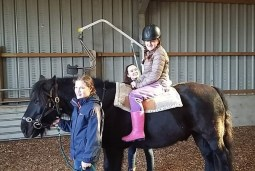 Little girl riding a horse assisted by specialist equipment