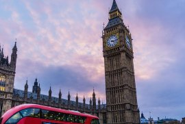 Image of the UK Houses of Parliament with a red double decker bus in front