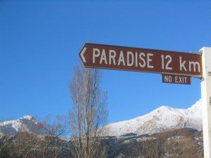 "sign-post saying ""paradise 12 km, no exit"" in front of blue sky and mountains"