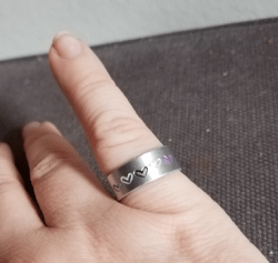 close-up of my right pinky with a silver ring with hearts in aro-ace pride colours
