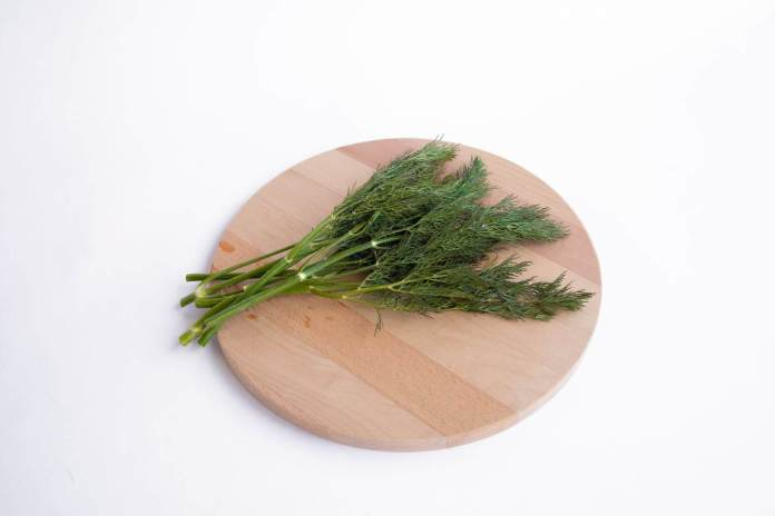 sprigs of fresh dill weed on cutting board