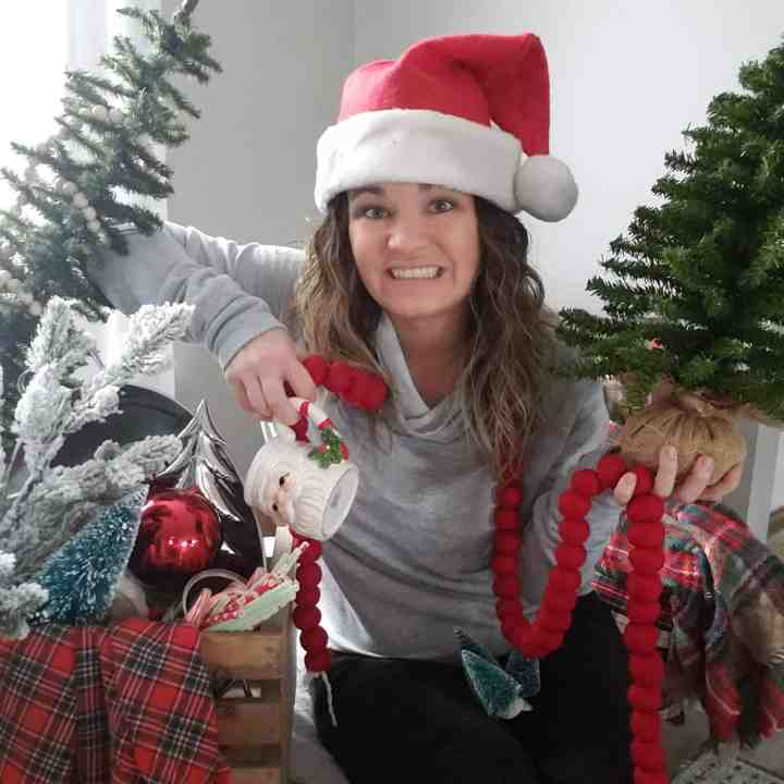 girl wearing santa hat while surrounded by christmas decor - post Christmas Organization guide