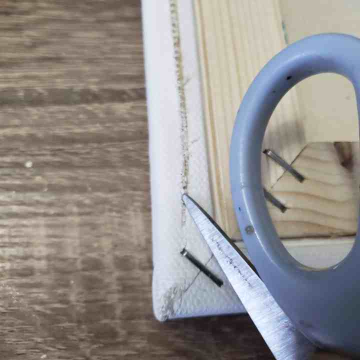 scissors cutting into the back of a canvas for a DIY Valentine's Day sign