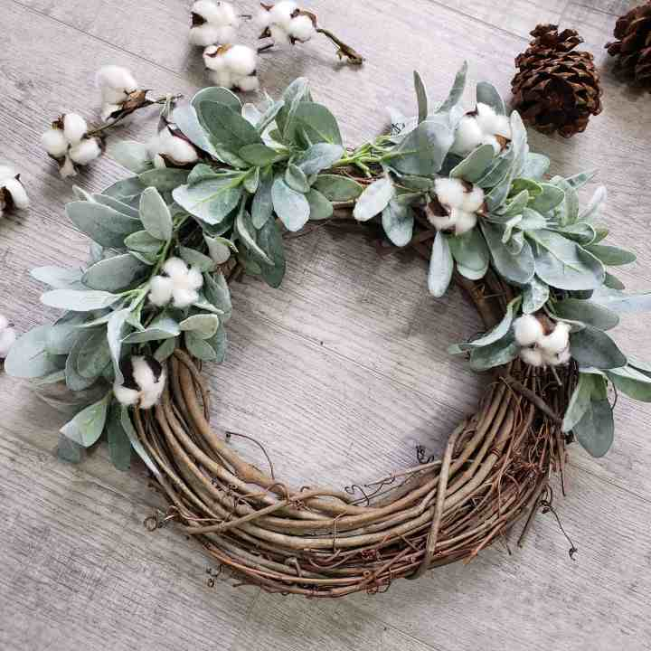 Winter wreath covered in greenery and cotton laying on gray flooring