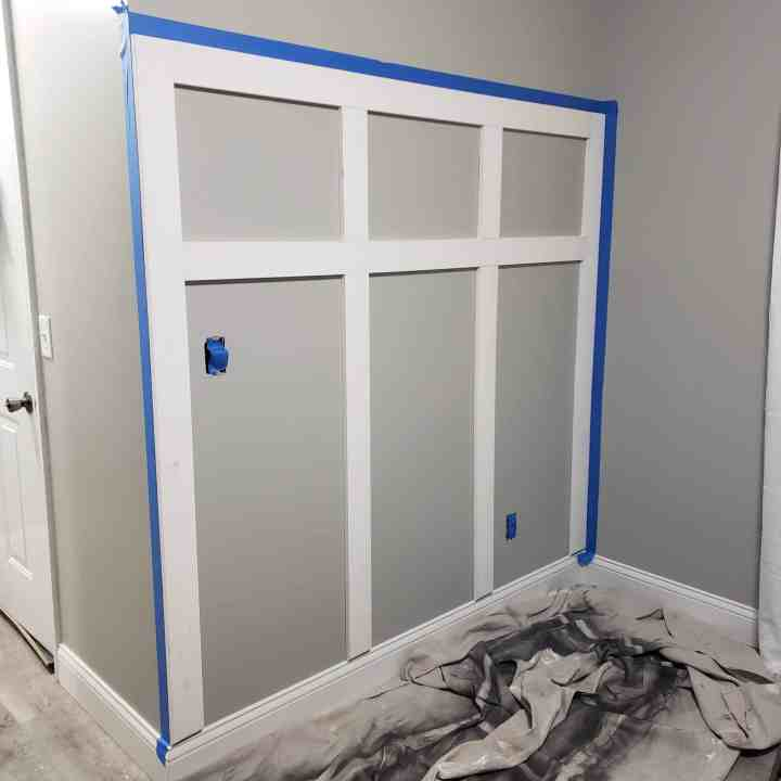 painters tape on wall to prep for painting to create white board and batten wall