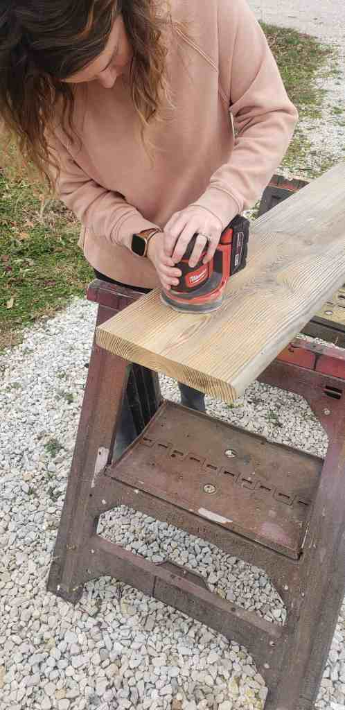 girl sanding a piece of wood with electric sander