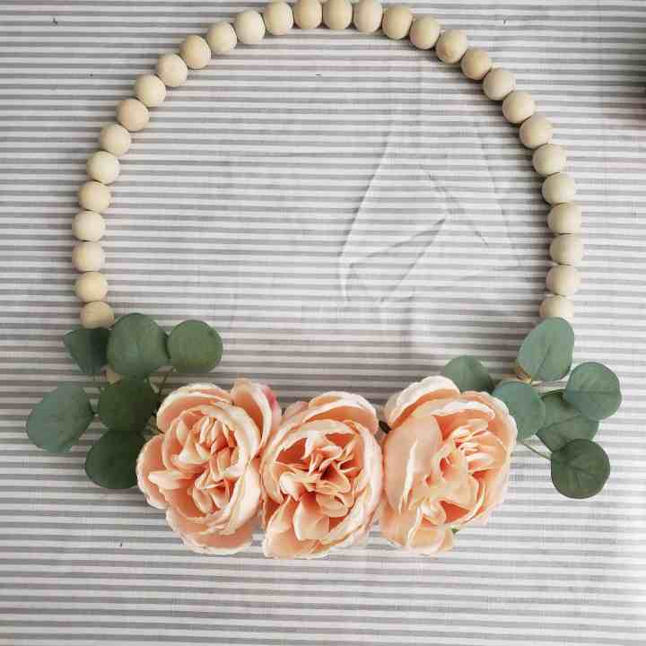 DIY Wood Bead Wreath with peach cabbage rose blooms and eucalyptus leaves