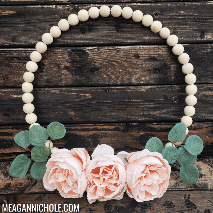 DIY Wood Bead Wreath with peach cabbage roses and eucalyptus leaves sitting against dark wood