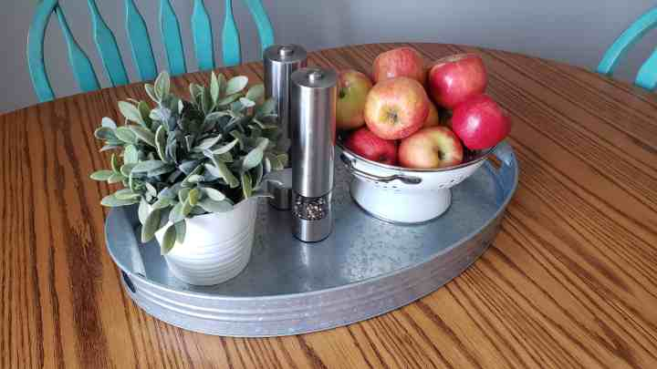 A metal tray holding a plant, bowl of apples, and salt and pepper for a kitchen table centerpiece blog post