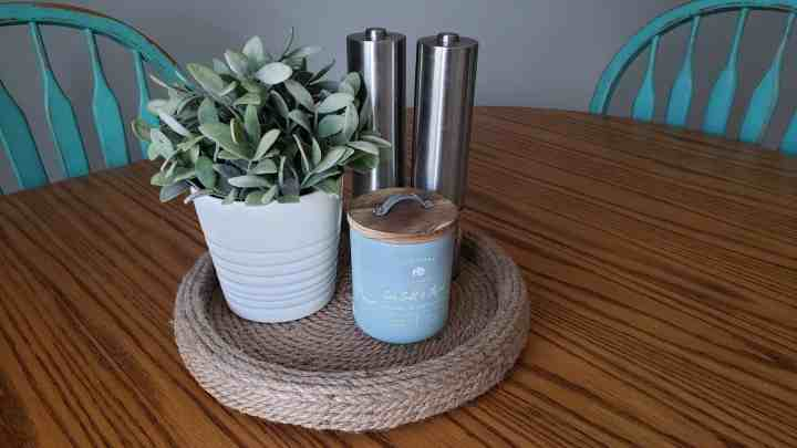 diy lazy susan holding salt and pepper, a plant, and candle for  a kitchen table centerpiece blog post