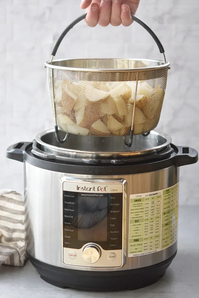 Diced potatoes in Instant pot basket held up