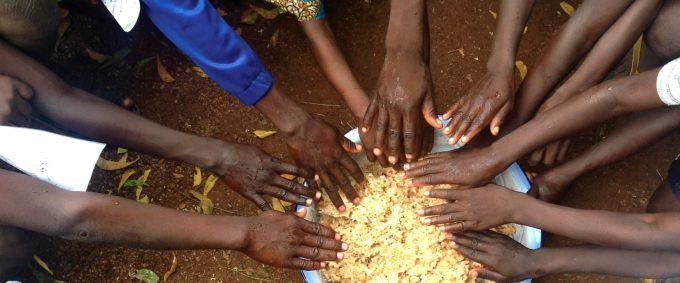 Hungry children around bowl of rice