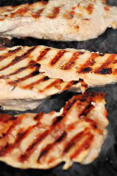 Chicken cooking on a plancha grill