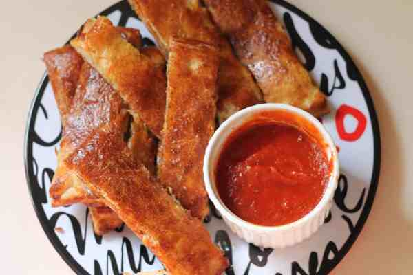 pepperoni bread sticks on a plate with marinara sauce