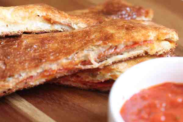 Pepperoni bread sticks and marinara sauce on a wooden board