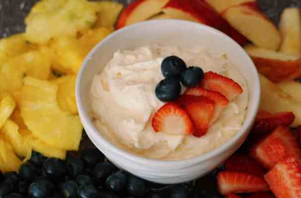 White bowl of fruit dip with strawberries and blueberries surrounded by apples, pineapple, blueberries, and strawberries
