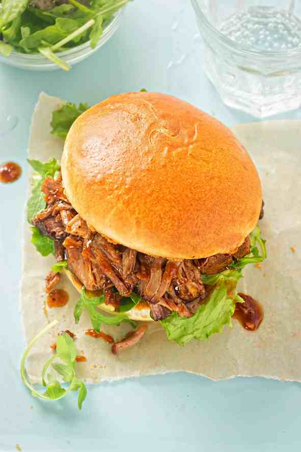 Pulled Pork Sandwich on hawaiian bun set upon a white napkin