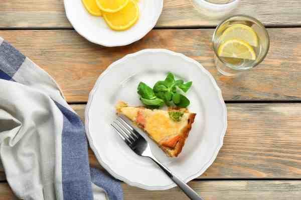 Salmon and goat cheese quiche on a white plate on a wooden table