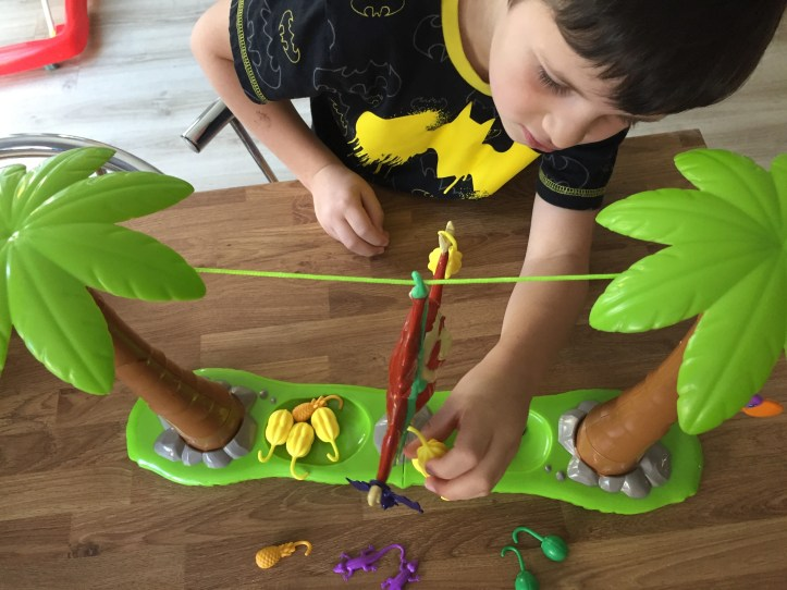 orangutwang board game - boy placing fruit on monkey