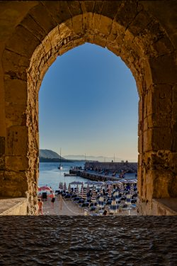 Looking through a stone arch to the beach in Cefalu