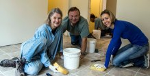 Susan, Gary & daughter working on the tile floor in one of the Habitat homes