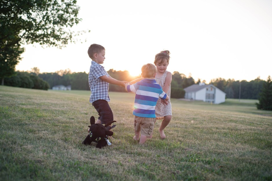 Three children playing in a circle in a grassy field, Babs Mullinax, me and grace, me & grace, Fort Wayne photographer, photo gifts, lifestyle photography, family photos, ideas for family photos, indoor photography, fun family photographer, long-distance family