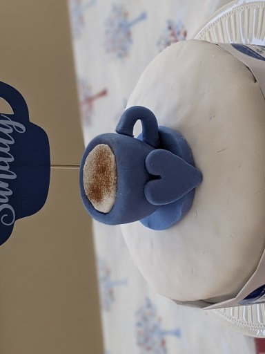 A white cake with a blue teacup on top