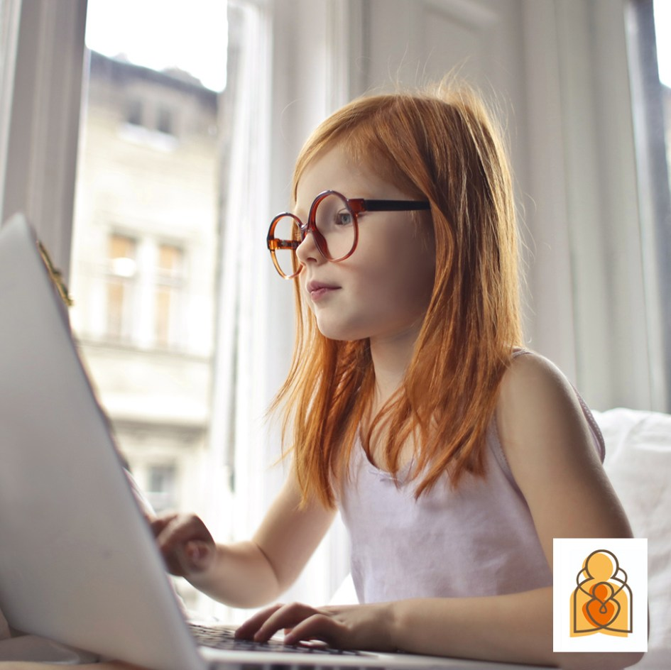 girl with glasses on computer by a window