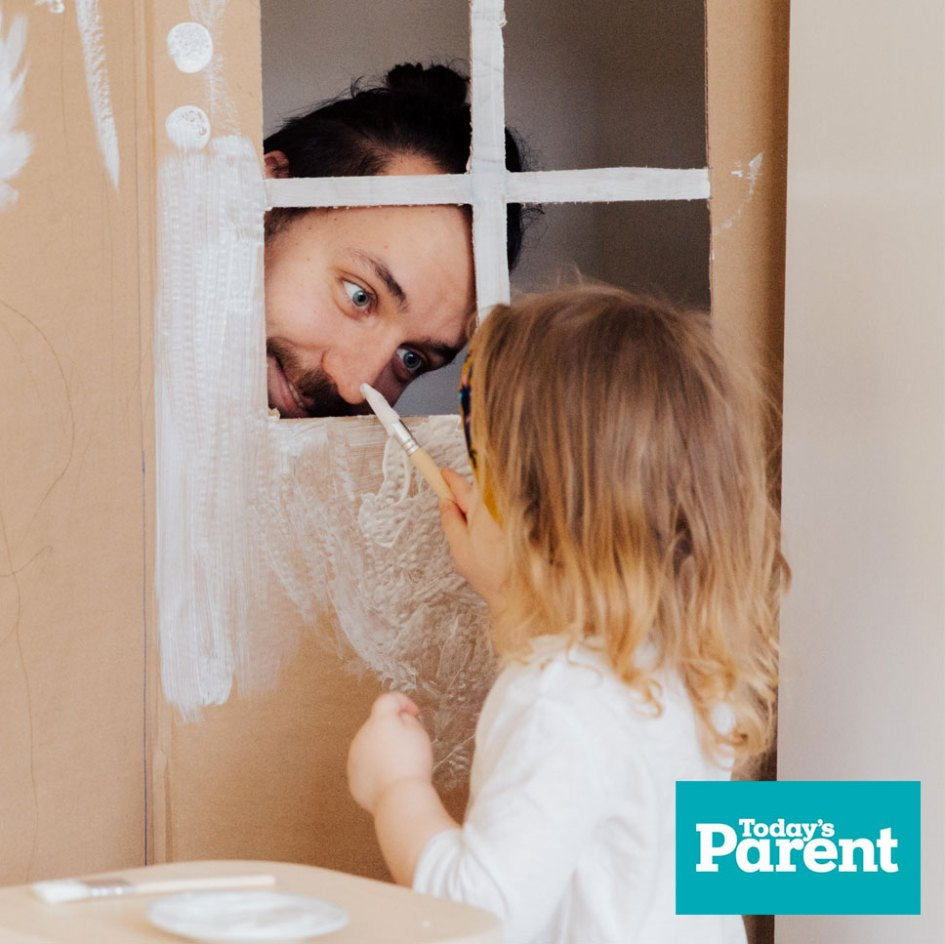 man playing with young girl in box with paintbrush