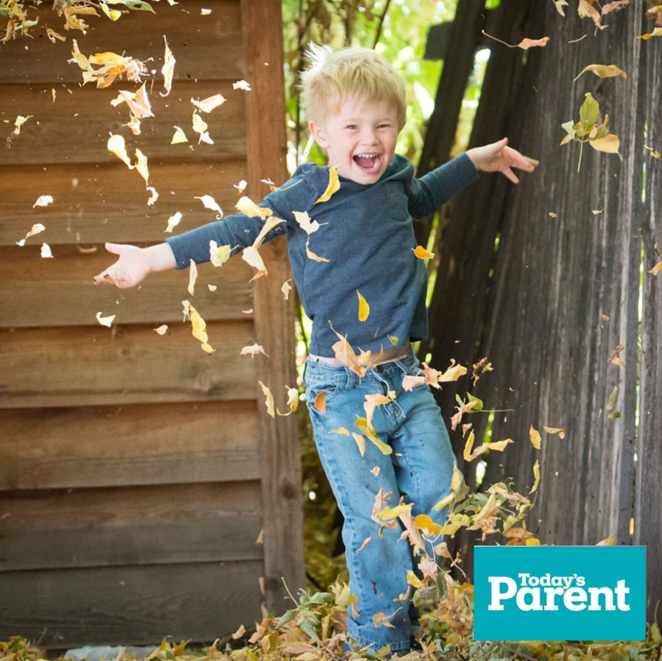 child jumping in leaves