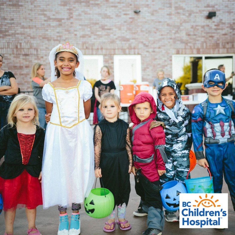 children standing together in halloween costumes