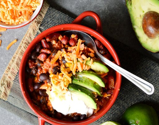 bowl of chilli with avocado and cheese on top