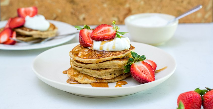 pancakes on white plate with strawberries and yogurt