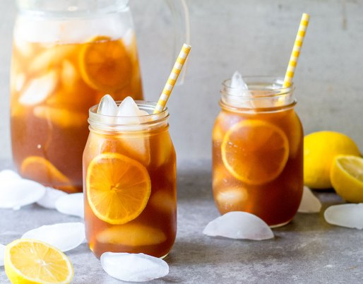 iced tea on table with lemons and glasses with straws