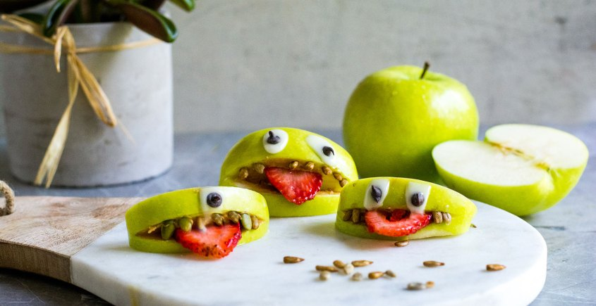 apple monsters on marble plate with green apple and sunflower seeds