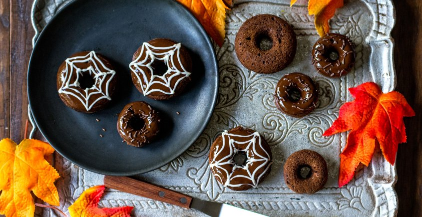 Spiders web donuts on tray with fall leaves